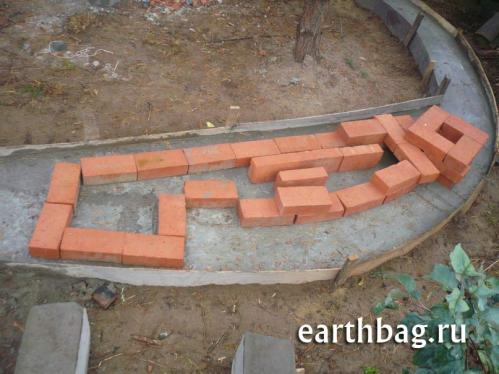 Mass heater fireplace built directly into the earthbag wall