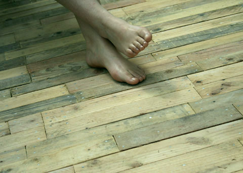 Outdoor deck made with pallet wood planks and pallets set on gravel