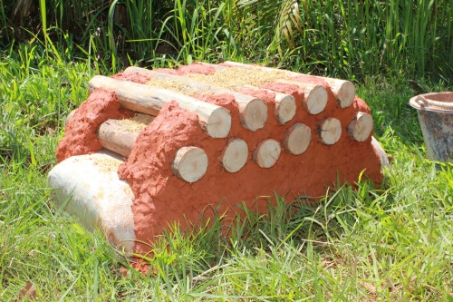 Demonstration wall showing cordwood stacked on earthbag bag foundation (click to enlarge)